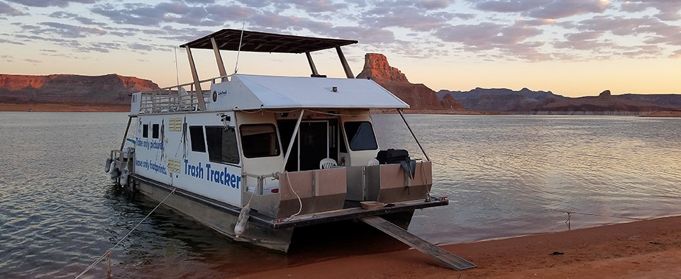 White houseboat labeled Trash Tracker beached during sunset.