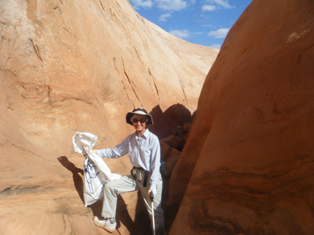 A woman in a hat and long sleeves holds a trach bag in one hand and grabbers in another as she smiles in a narrow canyon.