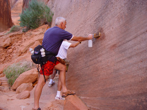 Two beople use squirt bottles and brushes to scrub graffiti off the canyon wall.
