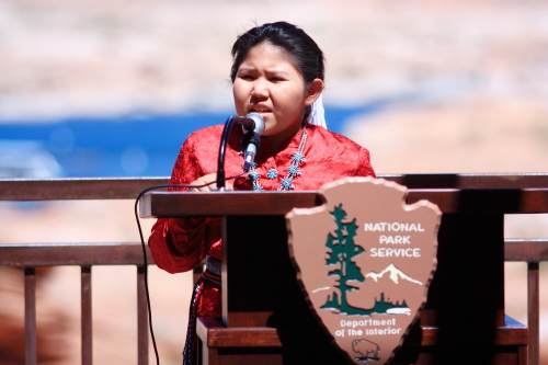 A young Navajo girl in native dress speaks at a podium with a National Park Service arrowhead on the front.
