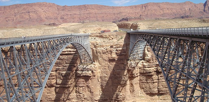 Two identical steel-arch bridges span across the canyon. A parking area on the other side.