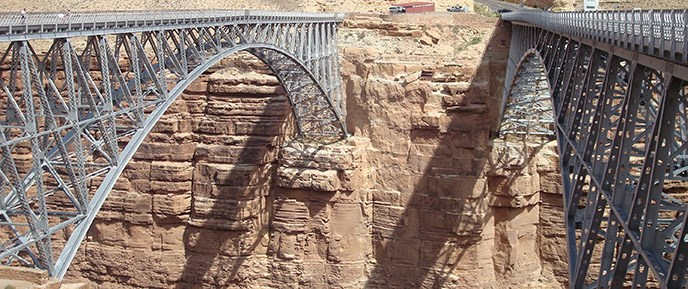 Two almost identical steel-arch bridges span the canyon. A parking area is on the other side.