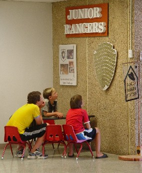 Three children sit at a tiny table and stare at Junior Ranger sign.