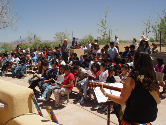 large group of kids, Park rangers, and a person playing guitar in open-air outdoor seating.