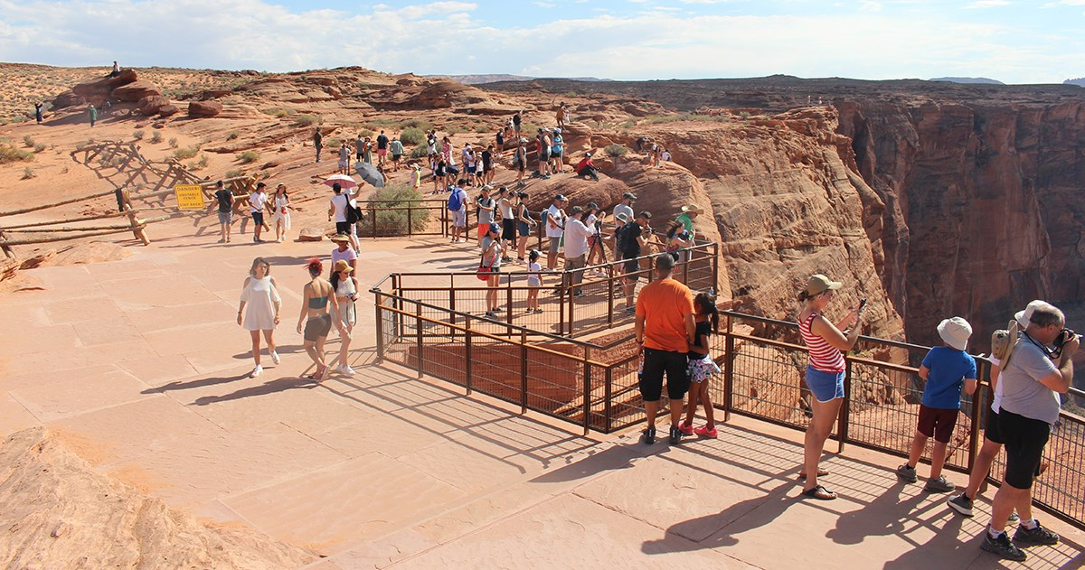 Large group of visitors on flagstone viewing platform at edge of canyon