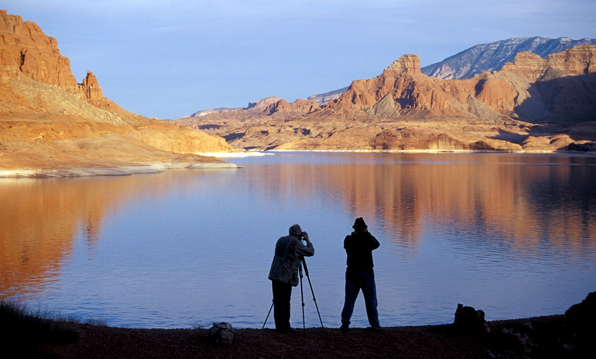 Two photographers in silhouette take photos of sunlit buttes reflected in lake