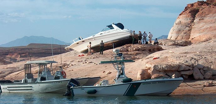A white boat is stranded on the rocks high above the water. Park Rangers and Sheriffs and their boats surround the area.