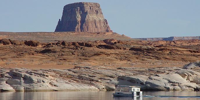 A large boat travels away from the camera towards a cliff wall. behind the cliff is a cylindrical butte.