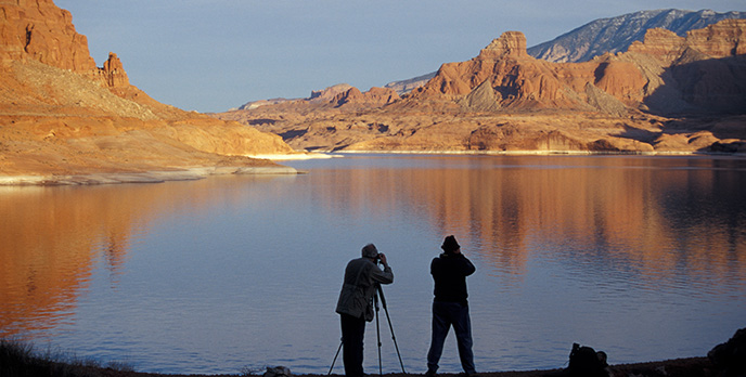 Silhouettes of two photographers taking pictures of cliffs and a mountain across the water.