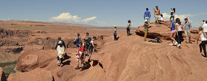 A large group of people stand on top of a sandstone rock. It's a long way down.