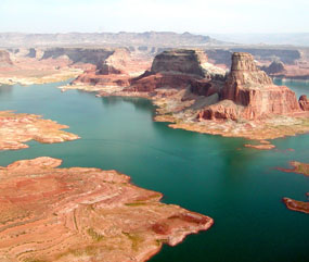 Aerial view of cliffs rising out of blue-green waters of Lake Powell.