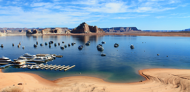 A sandy beach leads to still blue waters of Lake Powell. A large dock and may houseboats are in the bay. Behind them is a big sandstone cliff.