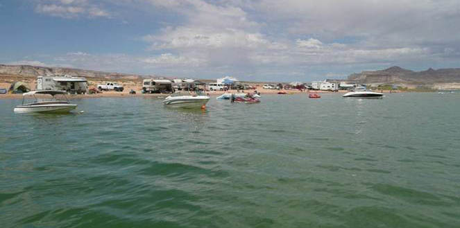 View from the water of a large group of boats near a sandy beach. The beach is full of campers, RVs, and tents.