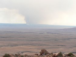 Smoke rises in the distance across a bare landscape.