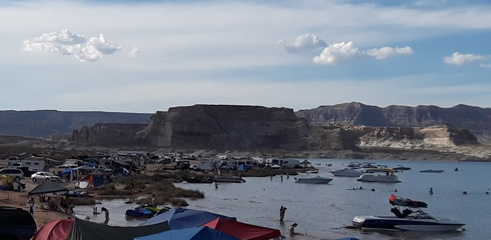 Beach full of vehicles, boats, and people