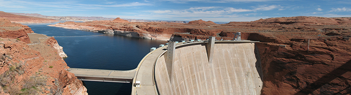 Long view of Glen Canyon Dam and lake Powell behind it.