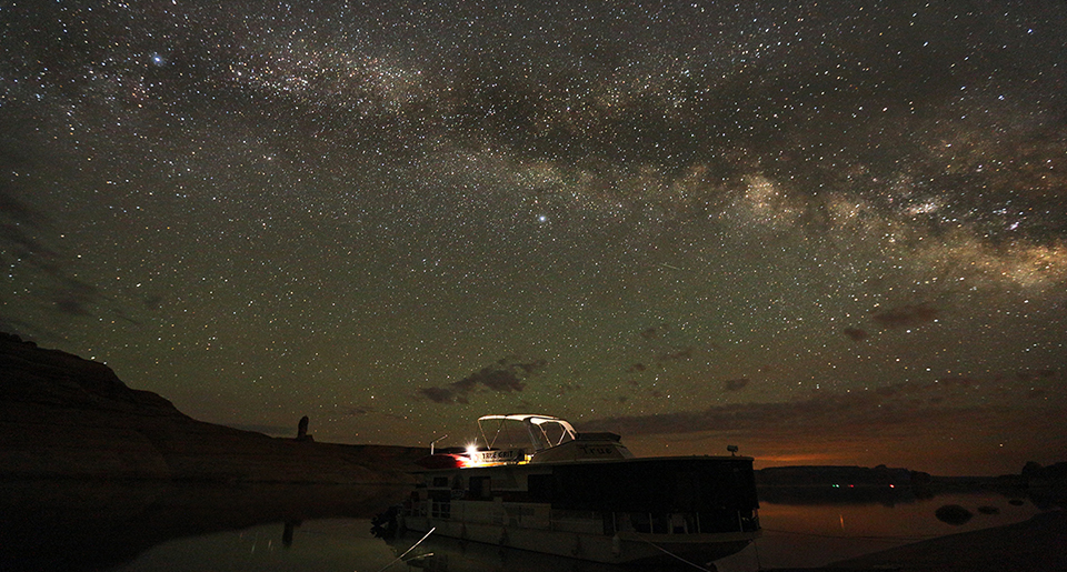 Houseboat beached at night with stars overhead.