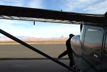 Man walks past plane in hangar with view of Tower Butte