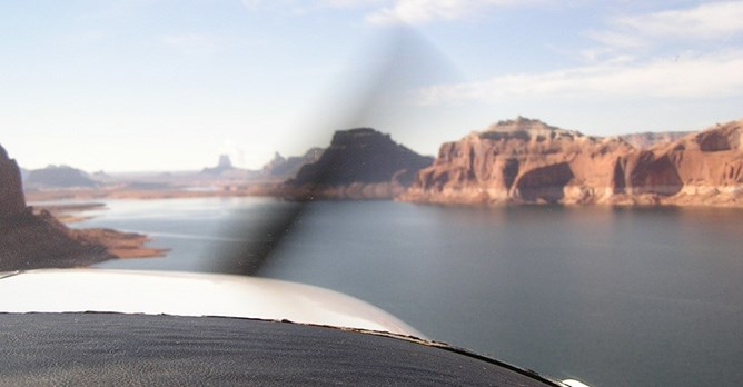 The front of a seaplane from the inside of the cokpit. The propeller is a blur. Lake Powell and sandstone cliffs lie ahead.