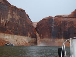 The bow of a boat looks at a muddy temporary waterfall off the side of a cliff into Lake Powell.