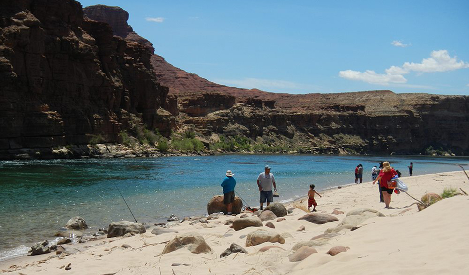 A river beach and a cliff, people fishing from shore.