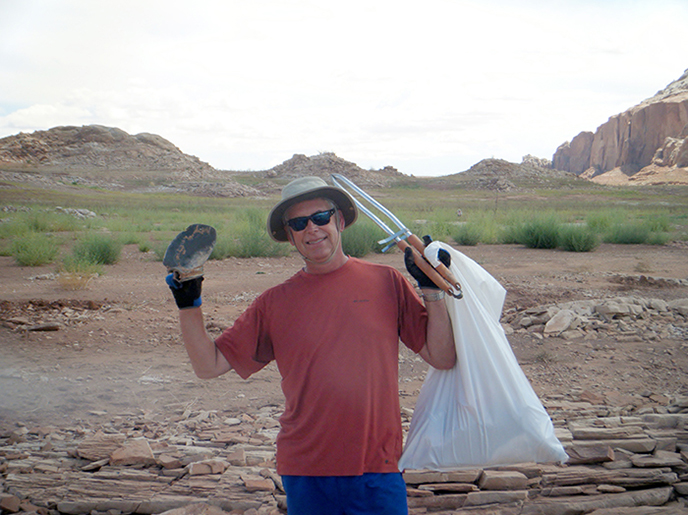 A man in a hat holds up a trash bag and grabbers.