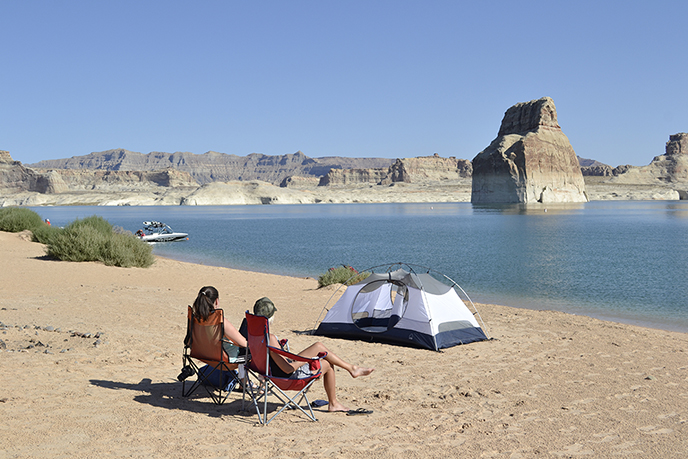 Two people sitting on a beach in front of a tent. in the water is a large rock structure. Cliffs in the background.