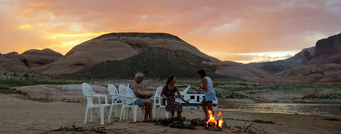three people sit in plastic chairs around a campfire on a beach. Houseboat and sunset in background.
