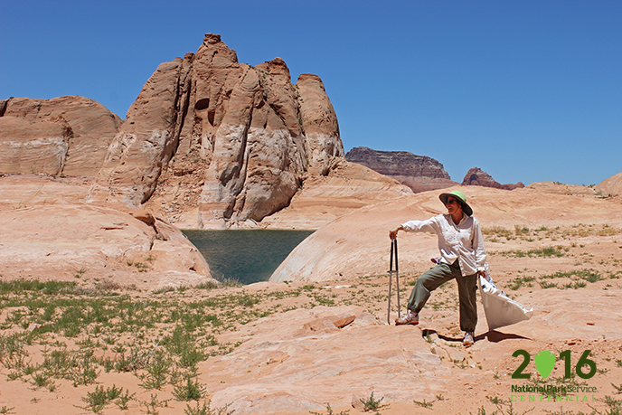 Woman with trash bag and grabbers looks at the sandstone and lake scenery.