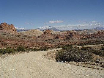 Dirt road winds past colorful buttes with snowy mountain in distance