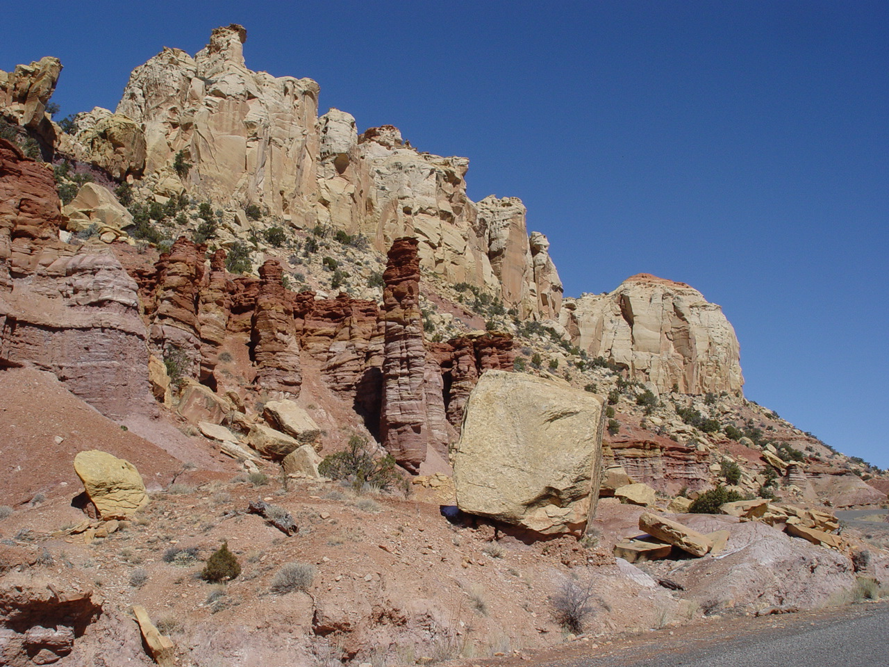 Multicolored cliffs rise above a paved road.