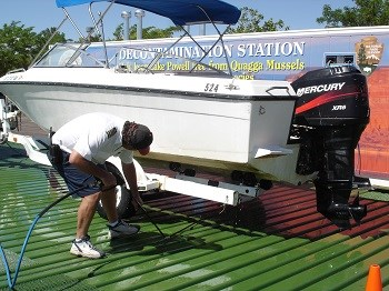 Man with power washer cleans underneath boat at park decontamination station