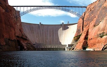 Glen Canyon Dam and bridge viewed from the Colorado River between tall sandstone canyon walls