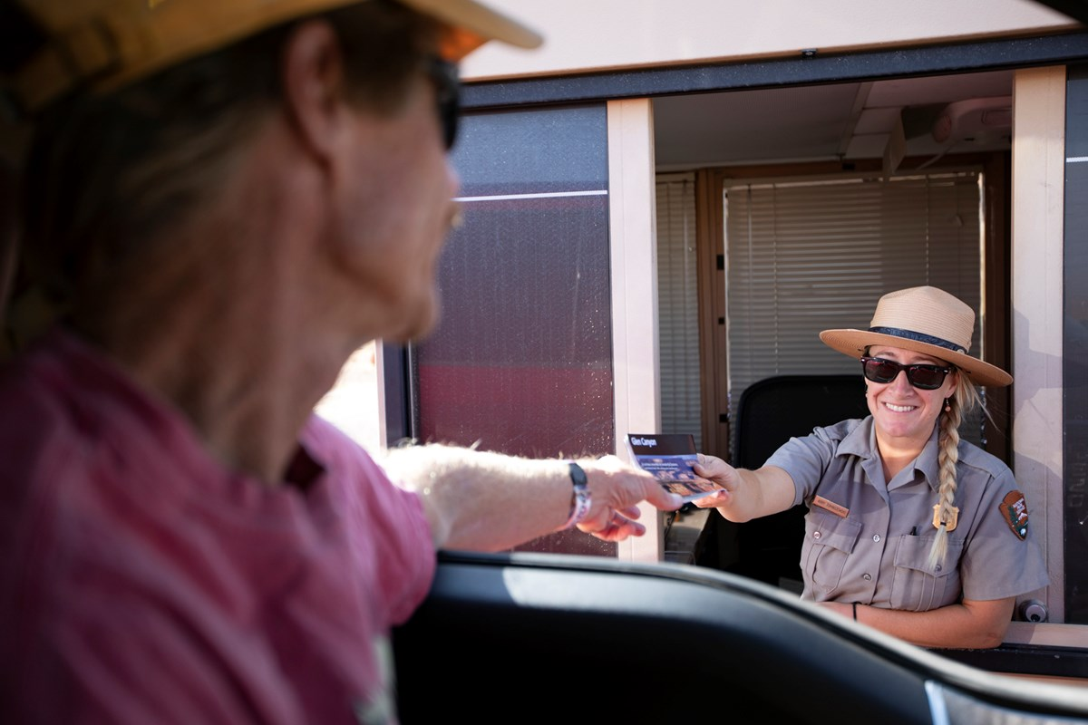 Ranger hands a brochure to a visitor behind the wheel of a car at at entrance booth