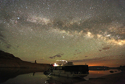 Night sky surrounds a houseboat on a beach.