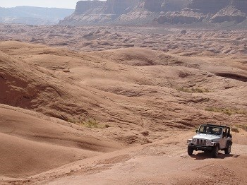 A jeep is dwarfed by surrounding red rock landscape