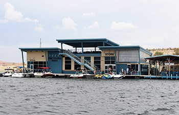 Boats docked outside floating building labeled Store with pavilion on top