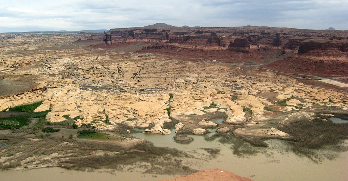 Looking down from high overlook on red mesas giving way to rounded sandstone formations leading to waters edge