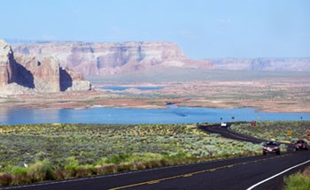 sandstone cliffs, lake, road with cars