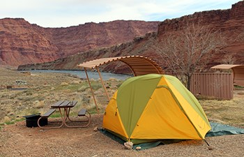 Tent set up by picnic table and curved shade shelter overlooking Colorado River in background
