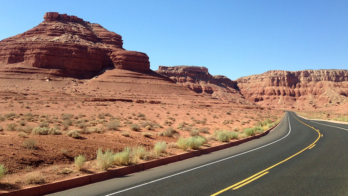 A paved road snakes by sandstone bluffs and cliffs
