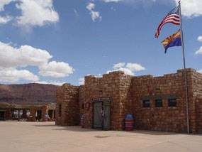 A chunky natural stone building flys the American and Arizona state flags. This is the Navajo Bridge Interpretive Center.