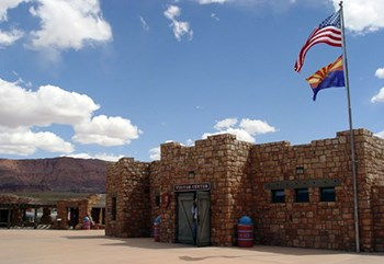A rustic natural stone building with barn doors flies the American and Arizona state flags.