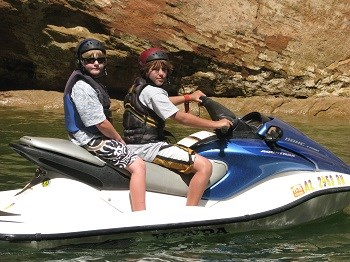 Two boys seated on personal watercraft wearing helmets and life jackets