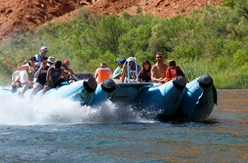 Smiling riders brace themselves for splashing water as they ride aboard a motorized raft