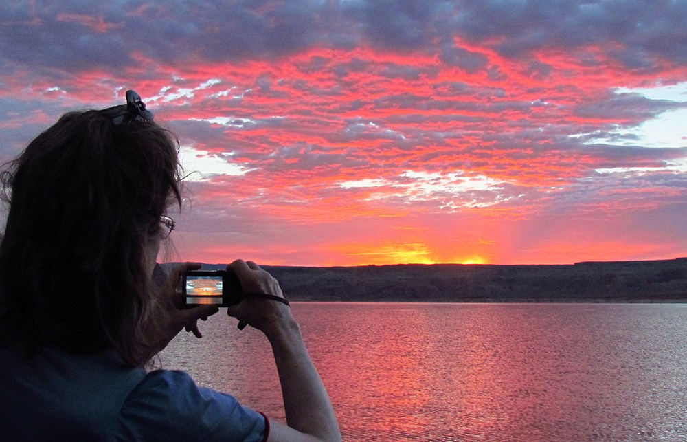 Woman photographs vibrantly colored clouds over lake. The image is repeated in her camera viewscreen.