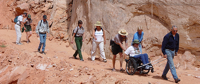 A group of people including two Park Rangers walks down a dirt trail next to a cliff. The person in the lead pulls a wheelchair while the person in the wheelchair operates the wheels and one of the Park Rangers pushes the chair from behind.