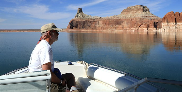 A man sits on a boat and stares at the water and cliffs.
