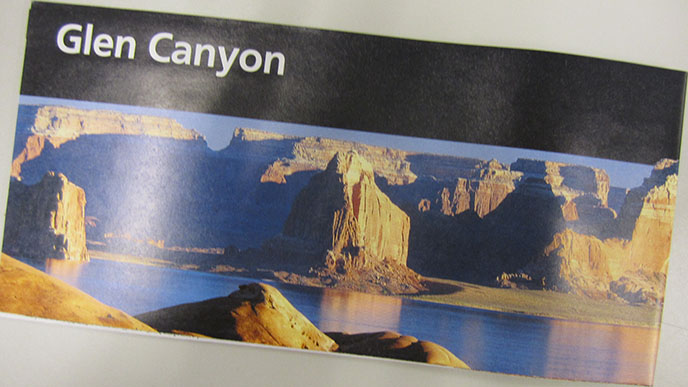 Image of Glen Canyon National Recreation Area's official brochure, with a black bar across the top and a picture of cliffs surrounding water.