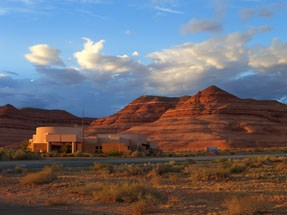 Orange cliffs and blue sky are behind a brown building. This is the Bullfrog Visitor Center.